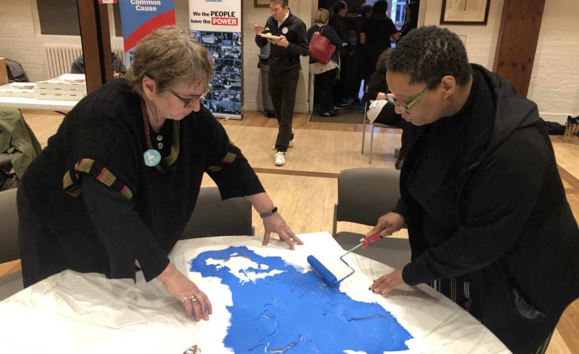 Sherri Davis (right), Common Cause Fellow, paints a gerrymandered district the night before a rally outside the Supreme Court.